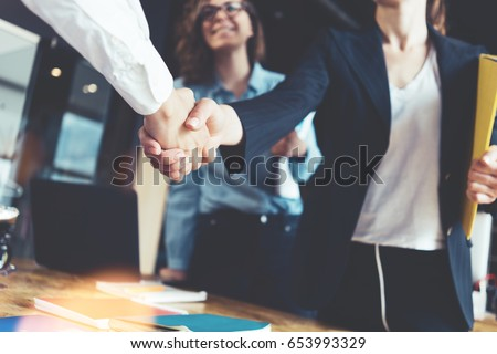 Young business people shaking hands in the office. Finishing successful meeting. Three persons Royalty-Free Stock Photo #653993329