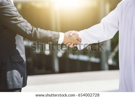 Business handshake concept. shaking hand of two businessman closing a deal city background  #654002728