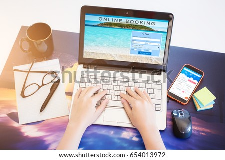 Browsing research network booking sites to book a vacation - Computer with various object on a desk #654013972