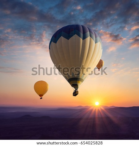 Morning in Cappadocia with hot air balloons in sunbeams at sunrise. Romantic travel for lovers couple or idea of wanderlust in retro style. #654025828