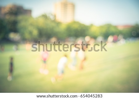 Blurred kids running, chasing each other on grass hill at sunset in summertime. Group smiling African American child running across hill urban park at Houston, Texas. Light, happy scene, vintage tone. #654045283