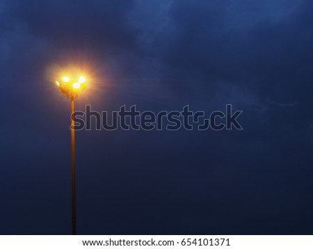 Street light pole on sky background while thunderstorm. Light fixture #654101371