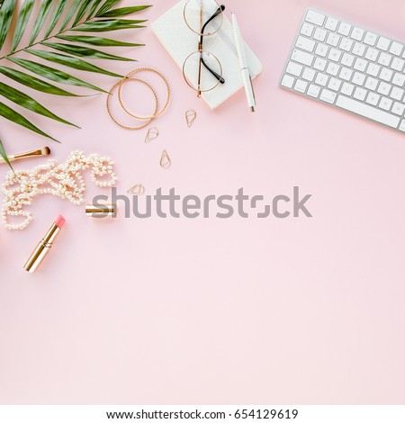 Office table desk with computer,  green leaves palm, clipboard. Magazines, social media. Top view. Flat lay. Home office workspace. Women's fashion accessories isolated on pink background.  #654129619