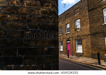 Typical old English buildings, low brick buildings across a narrow street, interesting old London architecture, english houses #654134335