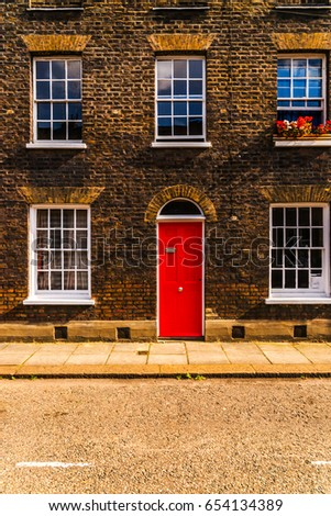 stylish entrance to a residential building, an interesting facade of the old brick arches above the door, a typical old English buildings, london #654134389