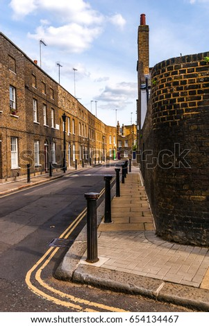 Typical old English buildings, low brick buildings across a narrow street, interesting old London architecture, english houses #654134467
