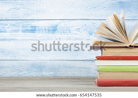 Open book, hardback books on wooden table. Back to school. Copy space for text. Education background.