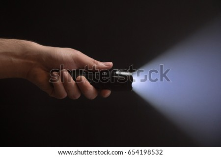 Black flashlight with wide beam in male's hand isolated from left side of the frame on black background Royalty-Free Stock Photo #654198532