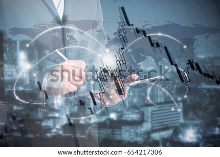 double exposure of businessman using tablet with blur city night and stockgraph. #654217306