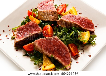 Fillet mignon - grilled beefsteaks with vegetables on white background  #654291259