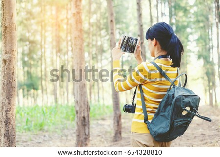 Young Woman in yellow sweater using tablet for take a photo between travel in pine forest. #654328810
