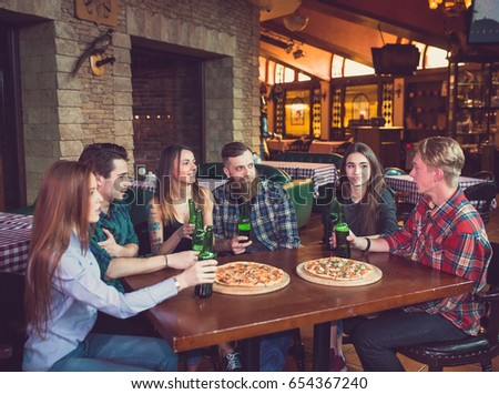 Friends having a drinks in a bar, They are sitting at a wooden table with beers and pizza. #654367240