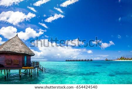 Maldives water bungalow on ocean water landscape #654424540