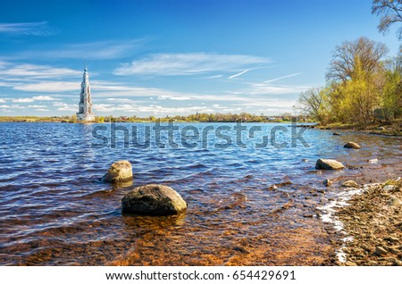 Flooded bell tower in Kalyazin on the Volga and rocks in the water and on the shore #654429691
