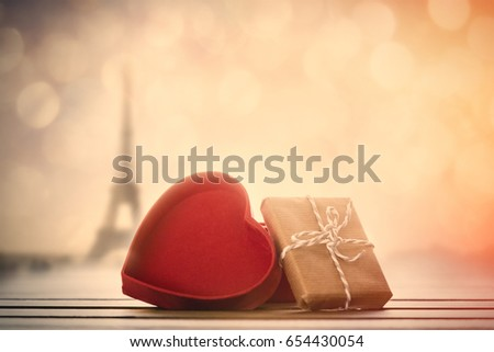Close-up view at heart shape box with Paris Eiffel Tower in bokeh at background #654430054