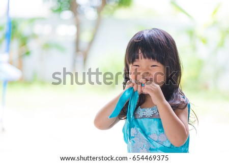Adorable Asian baby girl in blue dress, on white and green background. shallow focus. #654469375