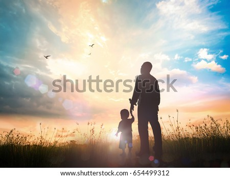 International migrants day concept: Silhouettes father and son holding hand in hand on meadow autumn sunset background Royalty-Free Stock Photo #654499312