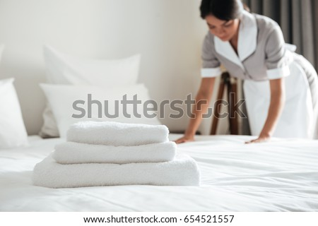 Young hotel maid making the bed with clean fresh towels #654521557