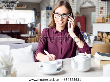 Woman at the cafeteria speak on phone. #654525631