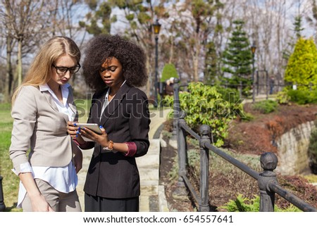 Two businesswomen looking at tablet screen. One woman is black. Women standing outside. #654557641