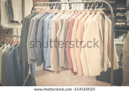 Suit shop, Raw of different colors man's suit or jackets hanging on apparel which blurred backgrounds. #654560020