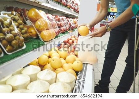 Man grabbing oranges from the shelf in supermarket #654662194