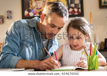 A father helps his little daughter to do her homework for the school. Royalty-Free Stock Photo #654676561