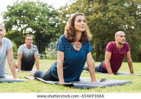Mature healthy people doing yoga at park. Group of multiethnic people exercising on green grass with yoga mat. Happy men and smiling women in yoga class doing exercise outdoor. #654691066