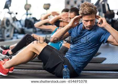 Muscular guy doing sit ups at gym with other people in background. Young athlete doing stomach workout in modern gym. Handsome fit man doing crunches at gym. #654691078