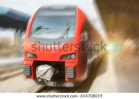 Modern high-speed train on a clear day with motion blur. Beautiful railway station with modern red commuter train. #654708019