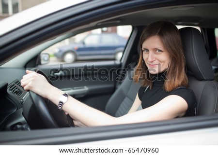 Pretty young woman driving her new car (shallow DOF; color toned image) #65470960