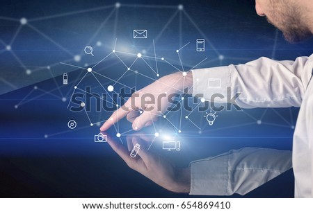 Male hands touching interactive table with blue mixed communication icons in the background #654869410