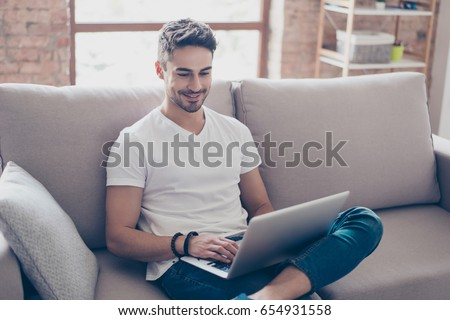 Young attractive smiling guy is browsing at his laptop, sitting at home on the cozy beige sofa at home, wearing casual outfit #654931558