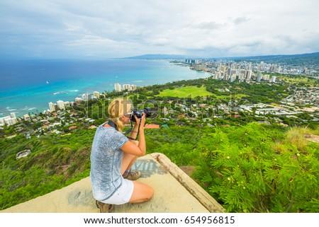 Travel photographer takes a shot of Honolulu and Waikiki beach, Oahu in Hawaii from Diamond Head State Monument. Nature photographer taking pictures outdoors during hawaiian hiking Diamond Head hike. #654956815