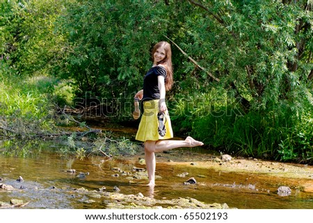 young woman crossing little stream in forest #65502193