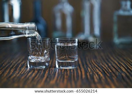Russian vodka pouring from the bottle into glass in a bar, selective  focus #655026214