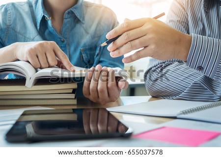 Young students campus helps friend catching up and learning tutoring. People, learning, education and school concept. Royalty-Free Stock Photo #655037578