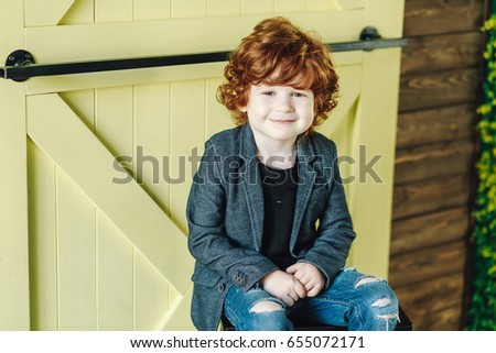 Smiling little boy in ripped jeans sitting on ladder and looking relaxed #655072171