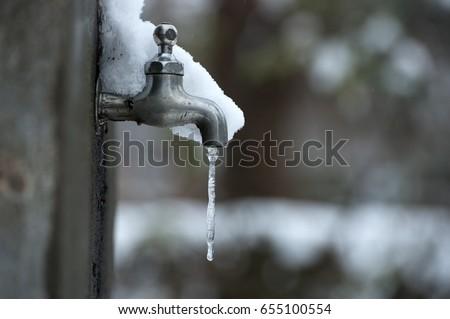 Freezing tap water Royalty-Free Stock Photo #655100554