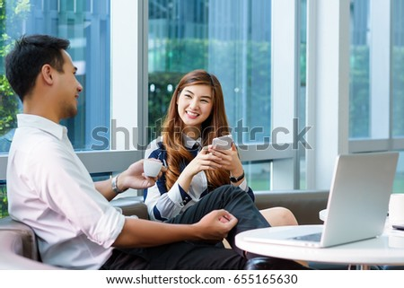 Asian charming beautiful business woman talking and discussing with her colleague in modern office or working space. Project and Business concept. Royalty-Free Stock Photo #655165630