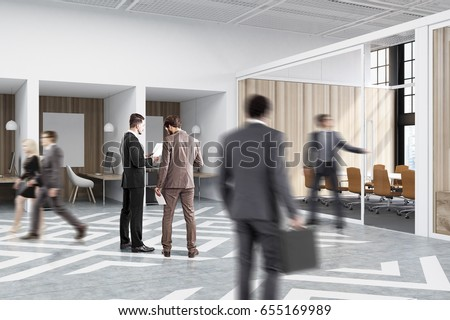 People near office cubicles in an office with white and wooden walls. There are blank vertical pictures in each of them, a desk with a computer, a chair and shelves.