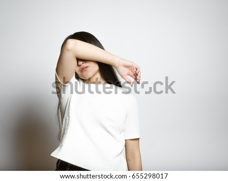 Young sad woman hides her face, isolated studio shot #655298017