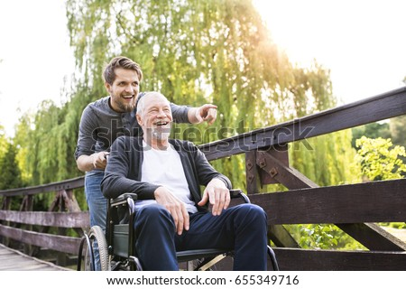 Hipster son walking with disabled father in wheelchair at park. Royalty-Free Stock Photo #655349716