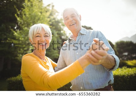 Portrait of happy senior couple dancing in park #655360282