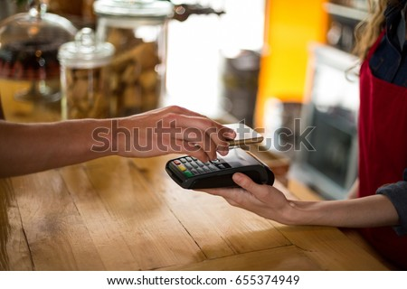 Man paying bill through smartphone using NFC technology in cafe #655374949
