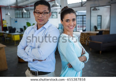 Portrait of smiling business colleagues standing back to back in office #655387858