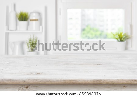 Empty textured wooden table and kitchen window shelves blurred background Royalty-Free Stock Photo #655398976