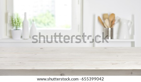 Wooden table on blurred background of kitchen window and shelves Royalty-Free Stock Photo #655399042