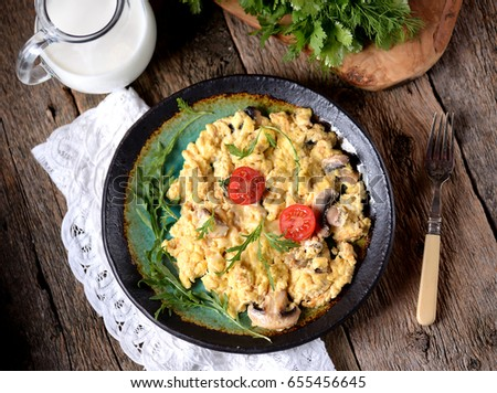 Scrambled eggs with mushrooms, cheese and green onions on an old wooden table. Rustic style. #655456645