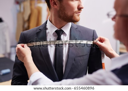 Mid section portrait of tailor fitting bespoke suit to model Royalty-Free Stock Photo #655460896